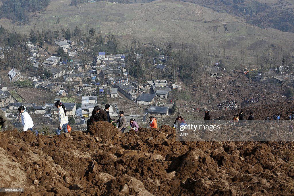 Local residents look at the buried area from the collapsed hill to see how the landslide happened in Gaopo village, southwest China's Yunnan province on January 12, 2013. Three people remain missing after a landslide which killed 43, including seven from a single family, struck a remote village in southwestern China, state media said on January 12.CHINA