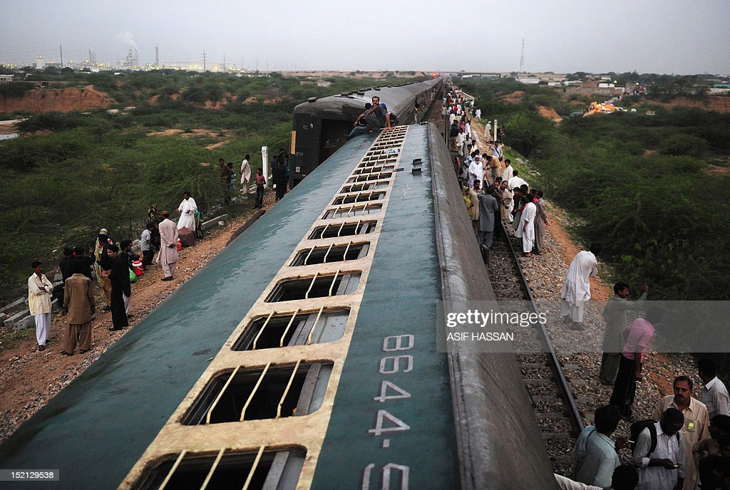 Local residents look at the derailed train compartments following a train accident in Bin Qaisim town, some 50 kilometers southwest of Karachi on September 17, 2012. At least two people were killed and dozens injured when two passenger trains collided near the Pakistan's southern port city of Karachi early on September 17, reported local media. AFP PHOTO / ASIF HASSAN
