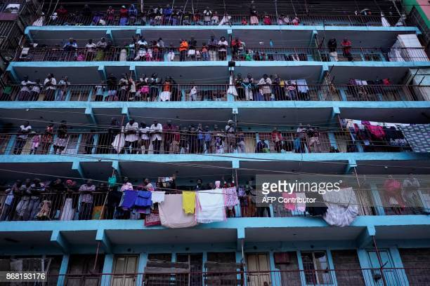 TOPSHOT Local residents look on from their balconies as opposition supporters set up a roadblock after the announcement of the reelection's result by...