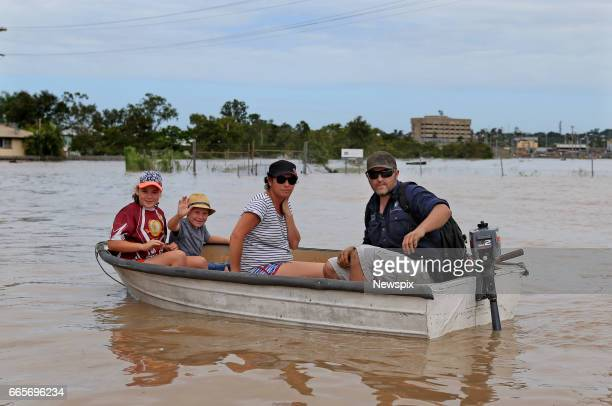 ROCKHAMPTON QLD Local residents Luke Lahrs and his partner Kim Yarrow and their children Harry and Gabby take their boat through floodwaters at Depot...