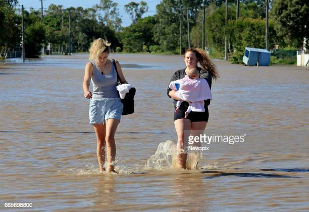 ROCKHAMPTON QLD Local residents Madison Tydd and Chloe Clements with her daughter Lily Rose wade through floodwaters at Depot Hill in Rockhampton...