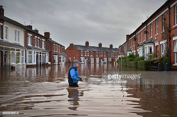 Local residents make their way through the flood water as they continue to leave their homes after severe flooding on December 7 2015 in Carlisle...
