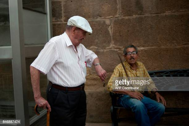 Local residents Miguel Canas and Jose Jimenez chat in Iznajar village on September 13 2017 / AFP PHOTO / JORGE GUERRERO