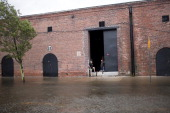 Local residents of Red Hook check their warehouse space along flooded streets August 28 2011 in the Brooklyn borough of New York City While Hurricane...