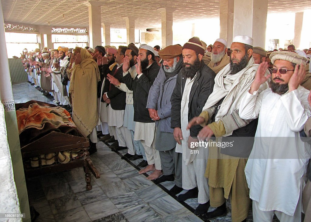 Local residents offer funeral prayers for a bomb blast victim in Mingora, the main town in the district, on January 11, 2013. An explosion at a religious gathering in Pakistan's northwestern Swat valley that killed 22 people and wounded more than 80 was caused by a bomb, officials said Friday. AFP PHOTO/STR