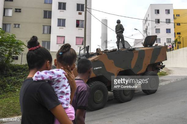 Local residents pass by a Brazilian Army VBTPMR Guarani armoured personnel carrier positioned on a street keeping watch during a predawn antigang...