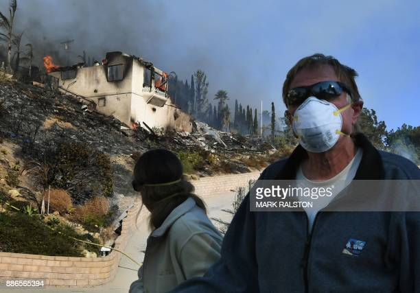 Local residents pass by a burning house during the Thomas wildfire in Ventura California on December 5 2017 Firefighters battled a windwhipped brush...