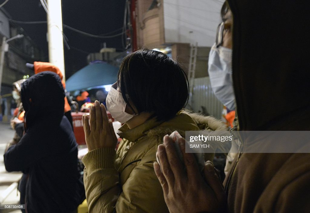Local residents pray for their relatives trapped inside a collapsed building as rescue personnel continue work at the site of a collapsed building in the southern Taiwanese city of Tainan on February 6, 2016 following a strong 6.4-magnitude earthquake. A powerful earthquake in Taiwan felled a 16-storey apartment complex full of families who had gathered for Lunar New Year celebrations in the early hours of February 6, with at least seven dead and more than 30 feared trapped. AFP PHOTO / Sam Yeh / AFP / SAM YEH