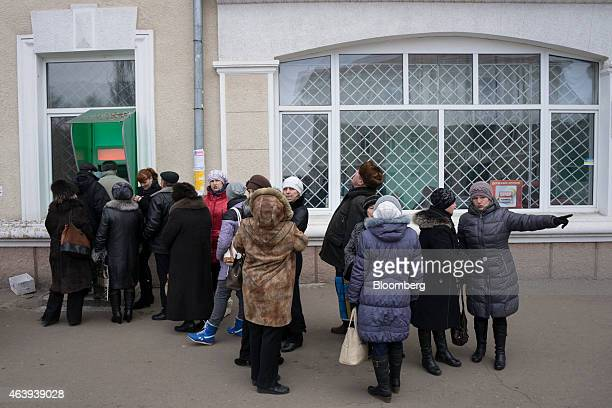 Local residents queue to withdraw hryvnia cash from an unbranded automated teller machine in Artemivsk Ukraine on Friday Feb 20 2015 Talks on...