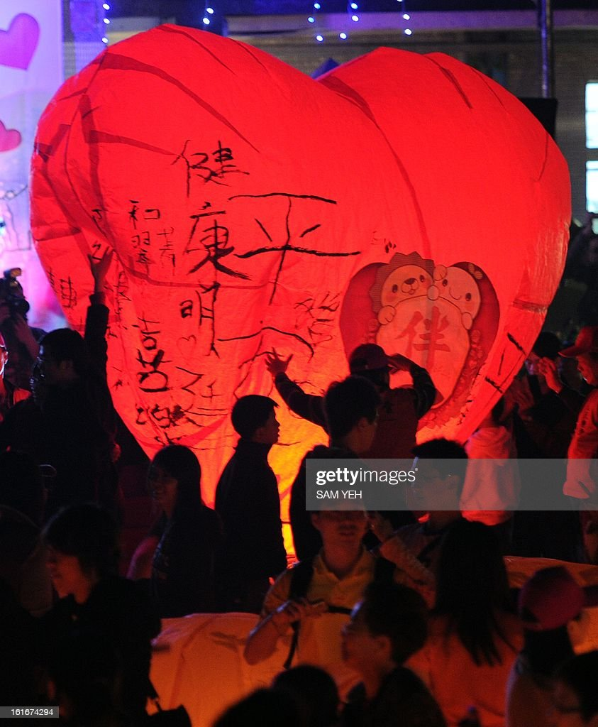 Local residents release a heart-shaped sky lantern in Pingshi, the New Taipei City, on the fifth day of the lunar new year on February 14, 2013. At least 600 couples celebrated their Valentine's day via releasing sky lenterns on the lunar new year of snake. AFP PHOTO / Sam Yeh
