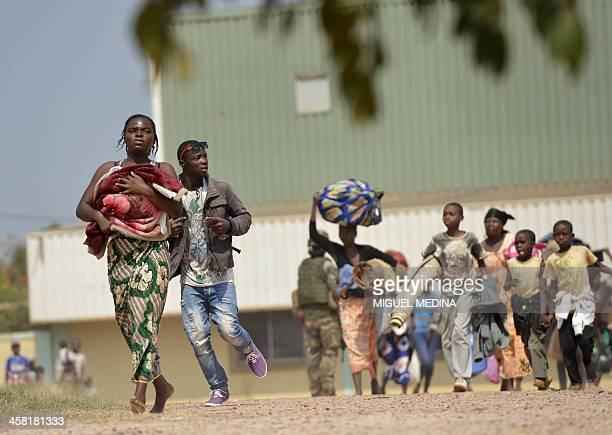 Local residents run for cover after hearing gunshots in the Combattant neighborhood in Bangui on December 20 2013 More than 30 people including a...