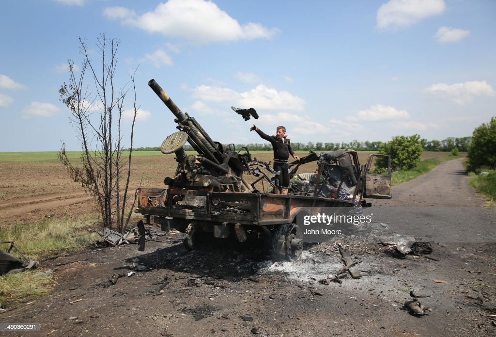 Local residents scavenge parts from a burnt Ukrainian military vehicle on May 14, 2014 in Dmytrivka, near Kramatorsk, Ukraine. Pro-Russian militants ambushed Ukrainian troops at the site the day before, killing seven and wounding another eight in the most deady attack yet on Ukrainian forces.