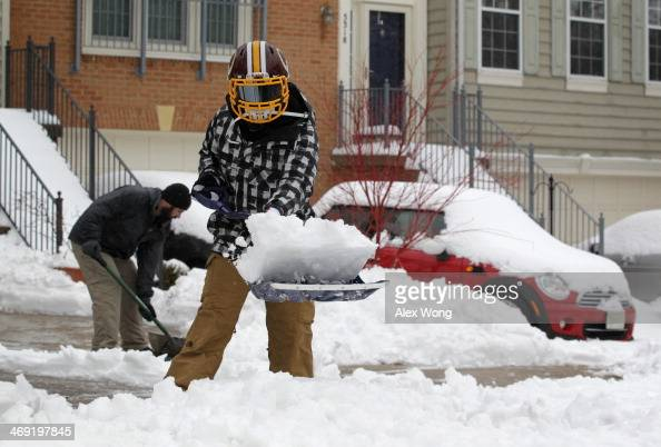Local residents shovel snow in front of their houses February 13 2014 in Alexandria Virginia The Washington DC area is embracing the biggest sown...
