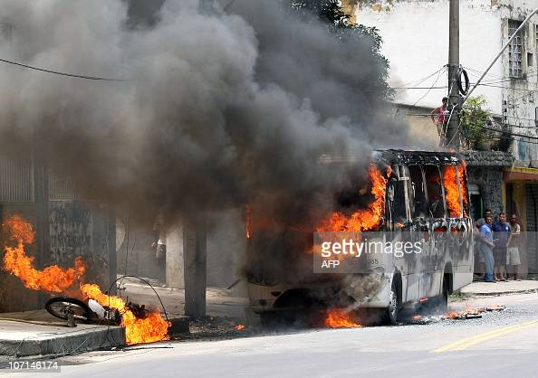 Local residents stare at a burning bus and motorcycle in Sao Goncalo Rio de Janeiro on November 25 2010 Drug dealers started a wave of attacks...