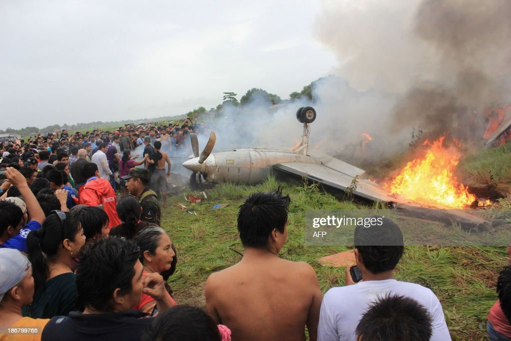Local residents surround the flaming wreckage of an Aerocon airlines Fairchild Metro 23 turboprop aircraft that crashed on landing in Riberalta, northern Bolivia, near the Brazilian border, on November 3, 2013, leaving eight passengers dead and 10 injured. AFP PHOTO/STR
