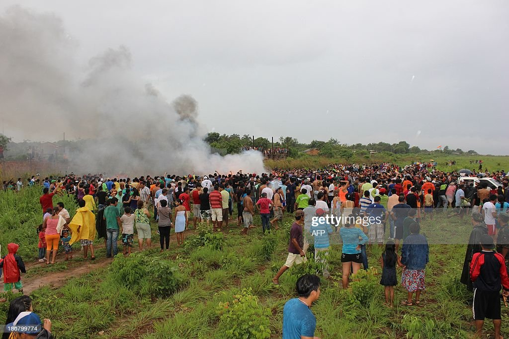 Local residents surround the flaming wreckage of an Aerocon airlines Fairchild Metro 23 turboprop aircraft that crashed on landing in Riberalta, northern Bolivia, near the Brazilian border, on November 3, 2013, leaving eight passengers dead and 10 injured.