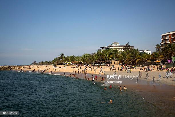 Local residents swim and sit on the beach in the Ilha district of Luanda Angola on Friday Nov 8 2013 Angola the largest crude oil producer in Africa...