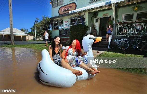 ROCKHAMPTON QLD Local residents Tahlia Thomasson and Tiona McGuigan play in the floodwaters outside the Fitzroy Hotel at Depot Hill in Rockhampton...