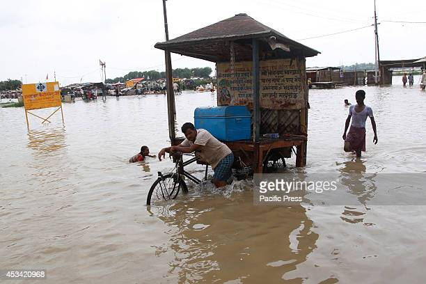 Local residents transporting materials on a rickshaw through a flooded roadway after the water level of Ganga increased in Allahabad Thousands of...