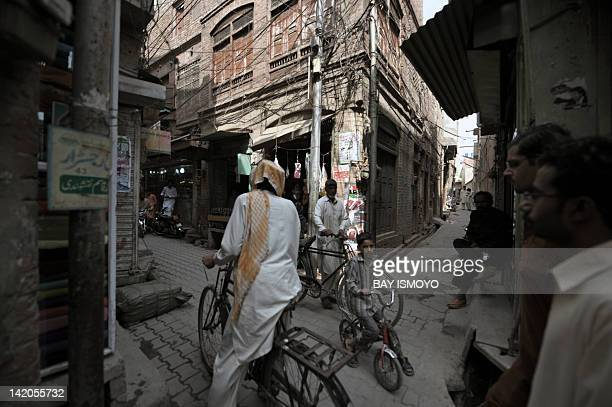 Local residents travel through narrow alleys past dilapidated buildings in the old town section of Multan on March 17 2012 Multan one of the oldest...