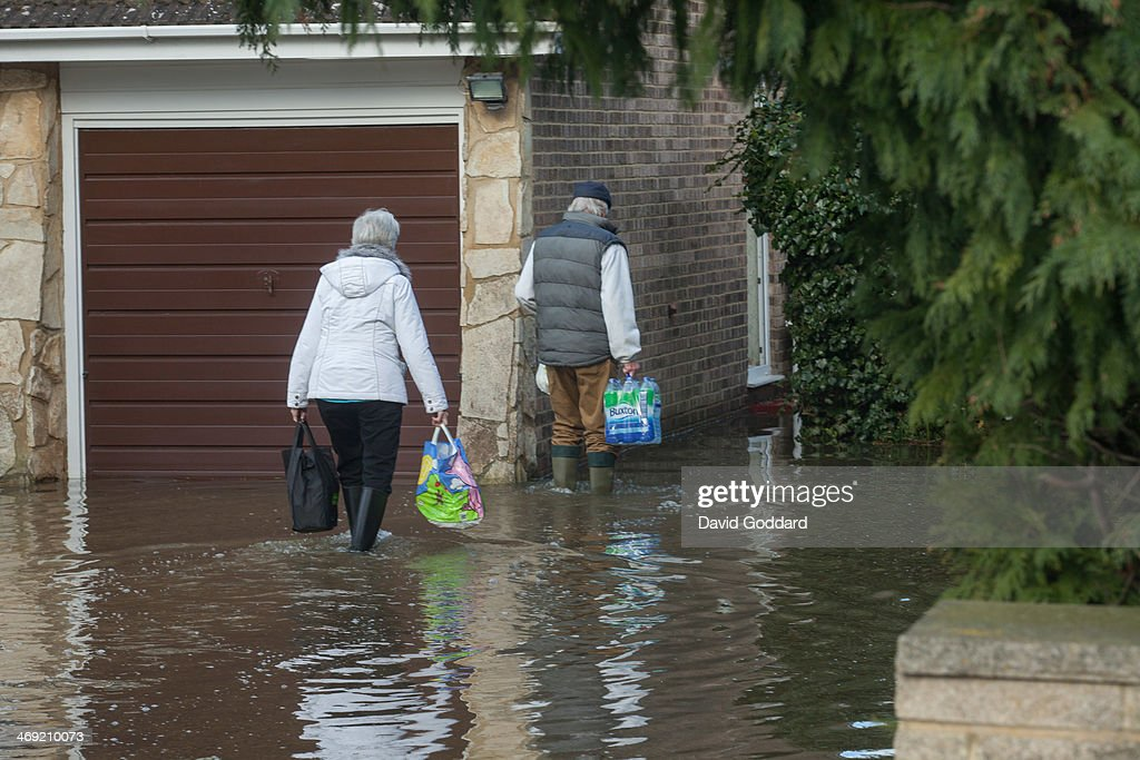 Local residents wade through the flood waters with supplies in the village of Wraysbury on the banks of the river Thames on February 13, 2014 in Wraysbury, England. The Environment Agency continues to issue severe flood warnings for a number of areas on the River Thames in the commuter belt west of London. With heavier rains forecast, people are preparing for the water levels to rise.