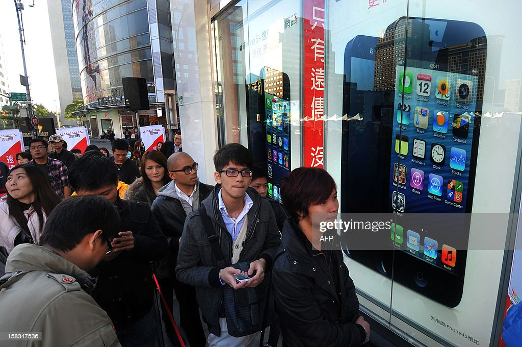 Local residents wait in line to purchase the Apple iPhone 5 outside a store in Taipei on December 14, 2012. Three main telecom companies released the lastest Apple iPhone 5 on December 14.AFP PHOTO / Mandy CHENG