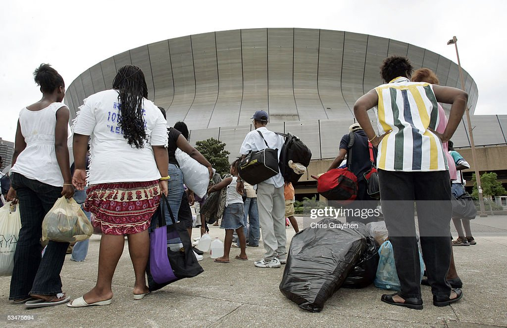 Local residents wait with their belongings for the New Orleans Superdome to open as an emergency shelter ahead of Hurricane Katrina August 28, 2005 in New Orleans, Louisiana. The storm is expected to make landfall in the morning of August 29.