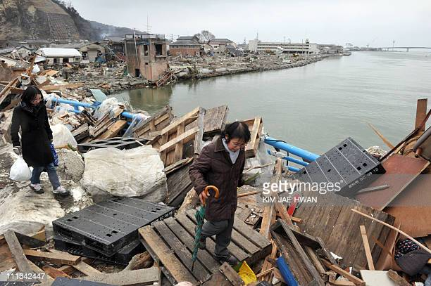 Local residents walk across a bridge covered with debris left by the March 11 tsunami in the city of Ishinomaki in Miyagi prefecture on March 15 2011...