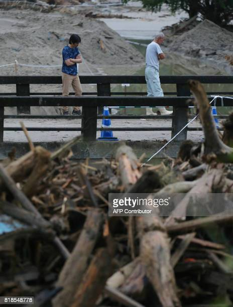 Local residents walk across a damaged bridge in a flooded area in Asakura city Fukuoka prefecture on July 19 two weeks after heavy rains and flooding...