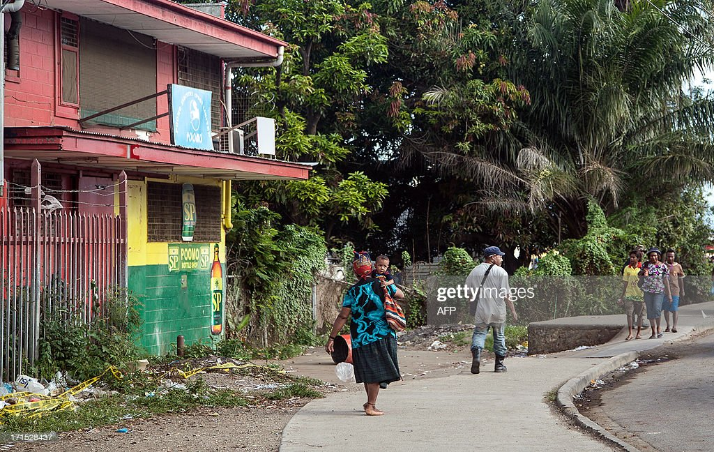 Local residents walk in front a bakery where four Asian expatriates were murdered in Port Moresby on June 26 2013 Four Chinese nationals have been...