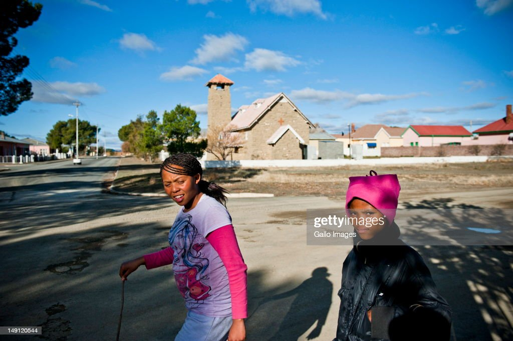 Local residents walk on July 20, 2012 in Carnarvon in the Northern Cape, South Africa. The town, which has a population of 6000, is the home of the KAT-7 telescope and will host the Square Kilometre Array radio telescope. Due to these developments the town's economy is growing.