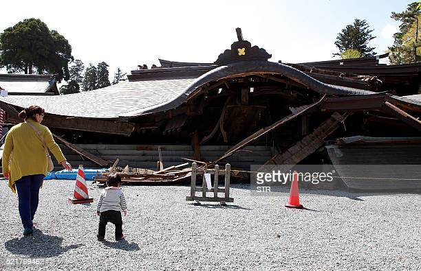 TOPSHOT Local residents walk past the 250yearold twostorey main gate of Aso Shrine which collapsed after the recent earthquakes in Aso Kumamoto...