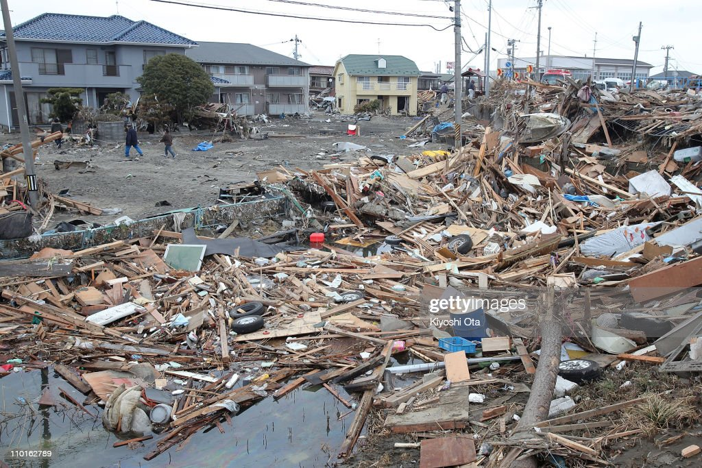 Local residents walk through an area damaged by tsunami after a 9.0 magnitude strong earthquake struck on March 11 off the coast of north-eastern Japan, on March 15, 2011 in Sendai, Japan. The quake struck offshore at 2:46pm local time, triggering a tsunami wave of up to 10 metres which engulfed large parts of north-eastern Japan. The death toll continues to rise with fears that the official death count could well reach up to 10,000 in 'the most tragic event in Japanese history since World War Two'.