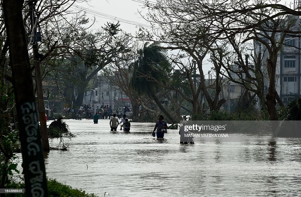 Local residents walk through floodwaters after cyclone Phailin made landfall at Gopalpur junction on October 13, 2013. Cyclone Phailin left a trail of destruction along India's east coast and up to seven people dead after the biggest evacuation in the country's history helped minimise casualties.