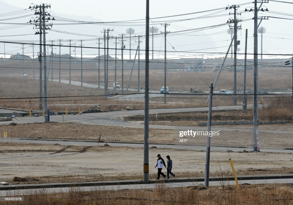 Local residents walk through vacant land to a tsunami memorial ceremony, one day before the second anniversary of the March 11 earthquake and tsunami disasters in Rikuzentakata on March 10, 2013. Japan will commemorate the second anniversary of a 9.0 magnitude offshore earthquake and giant tsunami that killed 15,880 people and left 2,694 unaccounted for, mainly in the Pacific coastline of the tohoku region in the nation's northeast.