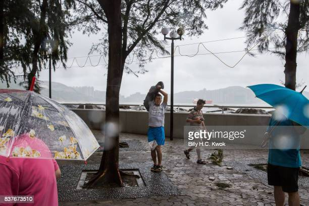 Local residents walks by the seaside as Typhoon Hato hits Hong Kong on August 23 2017 in Hong Kong Hong Kong Hong Kong's weather authorities raised...