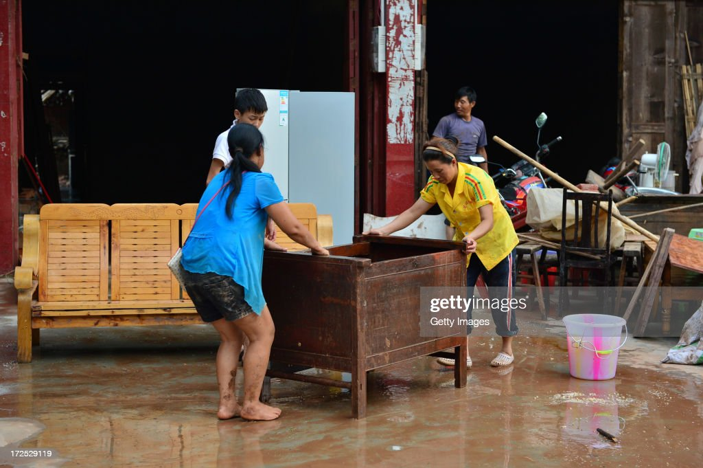 Local residents wash the mud from the furniture after flood waters receded on July 2, 2013 in Chongqing, China. More than 18,000 people were evacuated after rainstorms hit Tongnan county on Monday and triggered serious flood.
