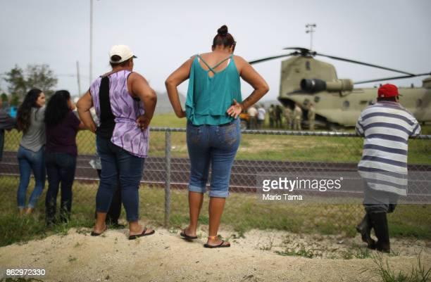 Local residents watch after a US Army helicopter landed during food and water delivery efforts four weeks after Hurricane Maria struck on October 18...
