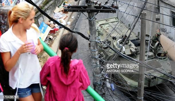 Local residents watch as Brazilian marines on an amphibious assault vehicle drive along a street of the Rocinha shantytown in Rio de Janeiro Brazil...