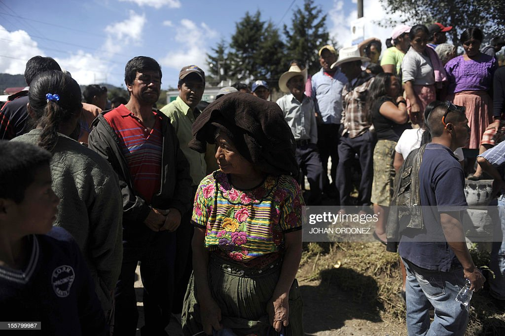 Local residents watch as firefighters with heavy equipment excavate searching people feared buried at a sand mine by an earthquake on the eve, in San Marcos, 260 km from Guatemala City, on <November 8, 2012. A 7.4-magnitude earthquake rocked southwestern Guatemala on Wednesday, killing 48 people and injuring another 150 while more were missing as homes crumbled. The earthquake also rattled nerves in neighboring Mexico and El Salvador, sparking a tsunami alert on the Salvadoran coast and evacuations from offices, homes and schools as far north as Mexico City. AFP PHOTO/Johan ORDONEZ