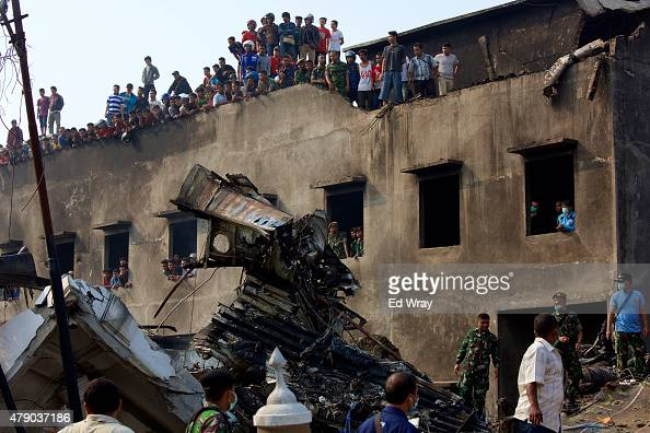 Local residents watch as military personnel and search and rescue teams comb through the wreckage of a military transport plane which crashed into a...