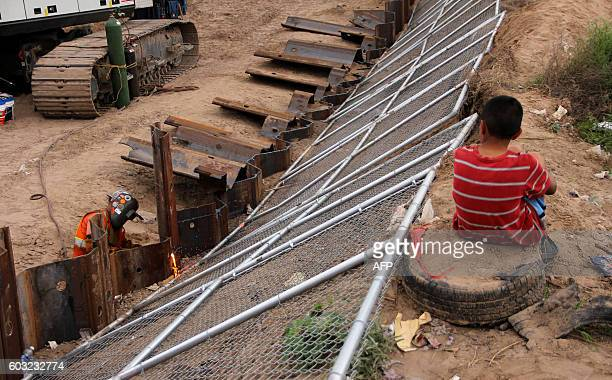 Local residents watch as US workers replace fencing with a higher new metal wall along the border between Ciudad Juarez and Sunland Park New Mexico...