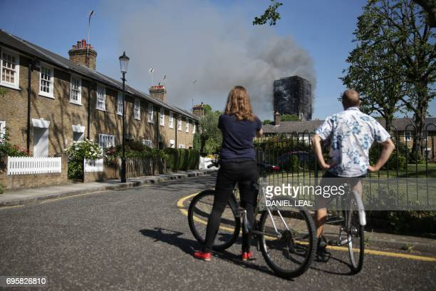 TOPSHOT Local residents watch smoke billow from Grenfell Tower a residential block on June 14 2017 in west London The massive fire ripped through the...