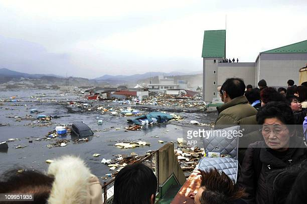 Local residents watch the devastation provoked by a tsunami tidal wave smashing vehicles and houses at Kesennuma city in Miyagi prefecture northern...