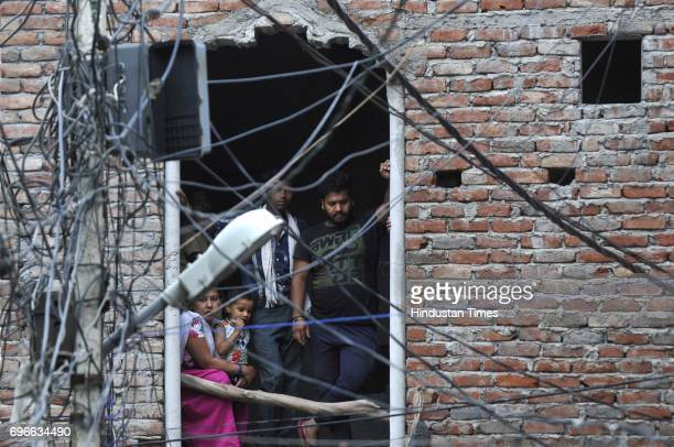 Local residents watching as bomb disposal squad at work after a bomb hoax inside a house in Sadarpur colony on June 16 2017 in Noida India A resident...