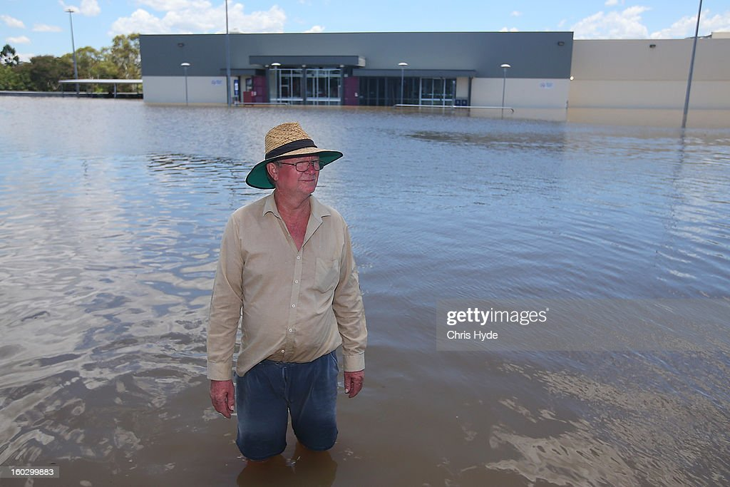 Local Robert Hicks stands on the roof of Hinkler shopping centre as parts of southern Queensland experiences record flooding in the wake of Tropical Cyclone Oswald on January 29, 2013 in Bundaberg, Australia. Four deaths have been confirmed and thousands have been evacuated in Bundaberg as the city faces it's worst flood disaster in history. Rescue and evacuation missions continue today as emergency services prepare to move patients from Bundaberg Hospital to Brisbane amid fears the hospital could lose power.