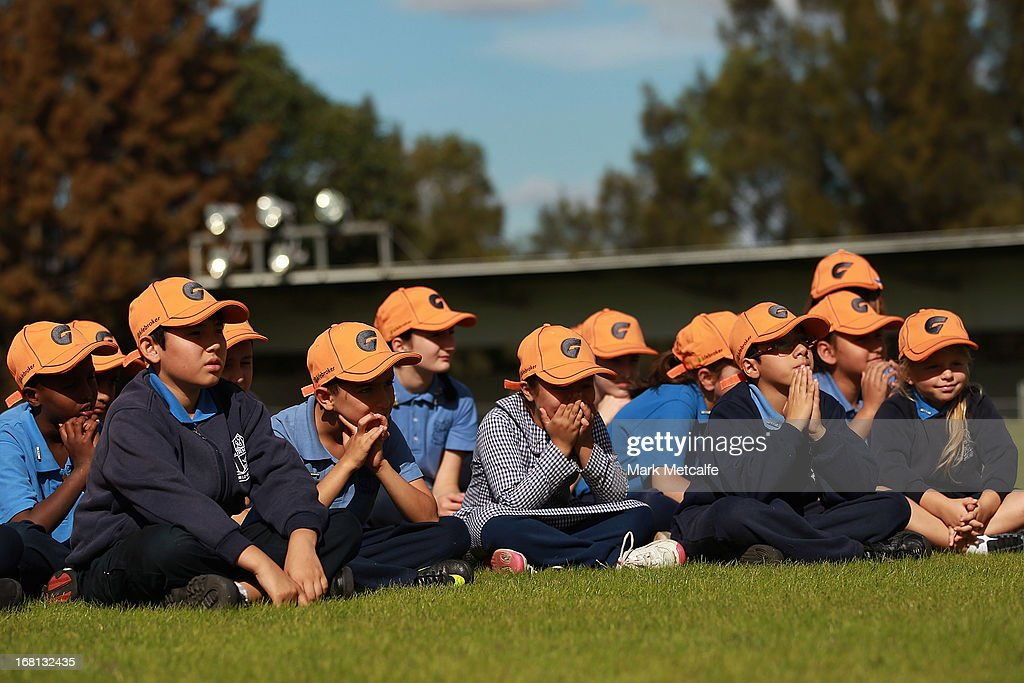 Local school children wearing GWS Giants caps look on during a GWS Giants AFL media session at Sydney Olympic Park Sports Centre on May 6, 2013 in Sydney, Australia.