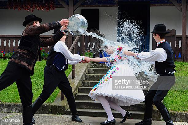A local school girl in traditional clothes of the 'Kalocsa' region react as boys throw water in Kalocsa some 100 km south of Budapest on April 17...