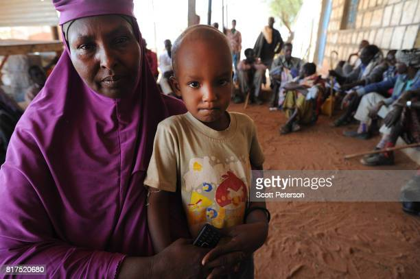 Local Somali coordinator Safiya Hassan Ibrahim holds her son Mubarak speaks about villagers who have benefited from food and cash donations mobilized...