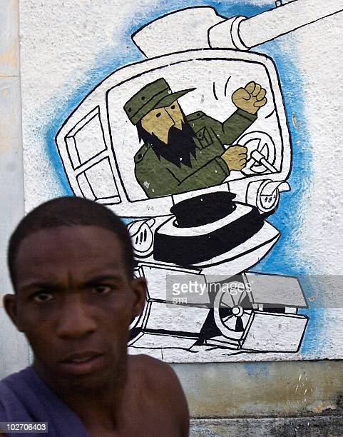 A local stands in front of a painting depicting Cuban former president Fidel Castro on August 11 2008 in Cotorro neighborhood in Havana Next August...